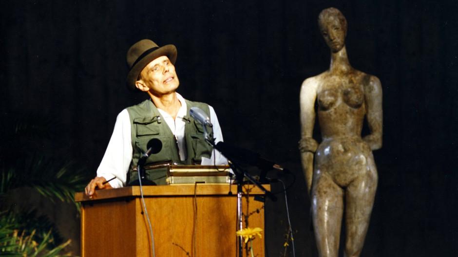 """Die Figur des """"Lehrers"""" hört aufmerksam zu: Joseph Beuys bei seiner Rede im Lehmbruck Museum Duisburg am 12. Januar 1986."""