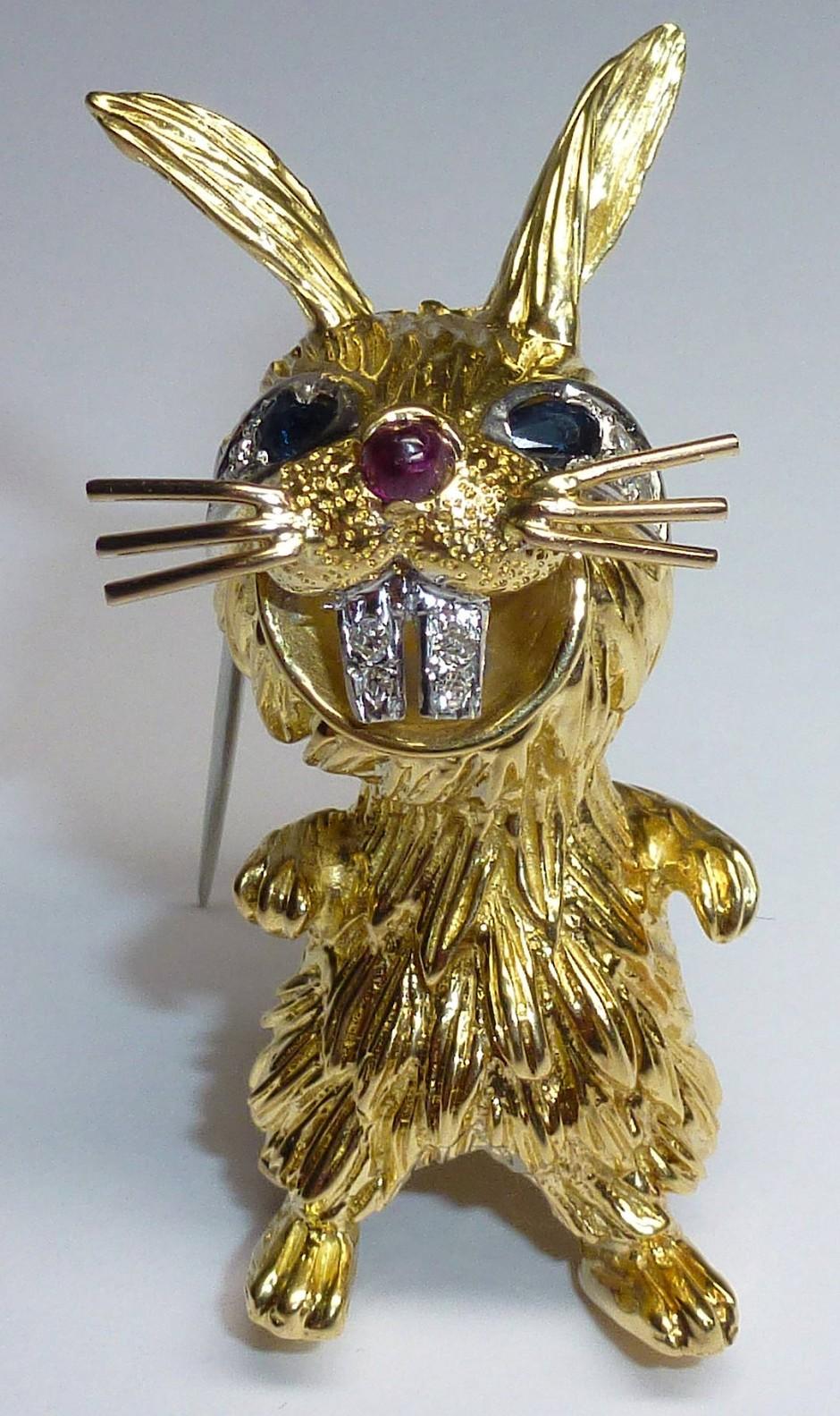 Goldene Brosche in Form eines Häschens, London 1970er Jahre, 18ct, geziert mit zwei Saphiren, einem Rubin und Diamanten, signiert: KUTCHINSKY, bei Pintar.