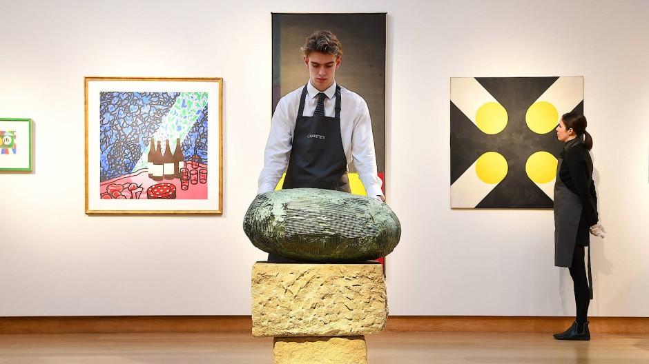 Ein Mitarbeiter von Christie's und Kunstwerke aus der Auktion mit moderner britischer Kunst im Januar 2020.