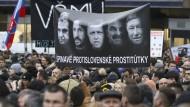"""Bürger begehren auf: Demonstranten halten während einer Kundgebung unter dem Motto """"Für eine anständige Slowakei"""" ein Plakat mit den Gesichtern von Ministerpräsident Robert Fico (Mitte) und Innenminister Robert (zweiter von rechts) hoch."""