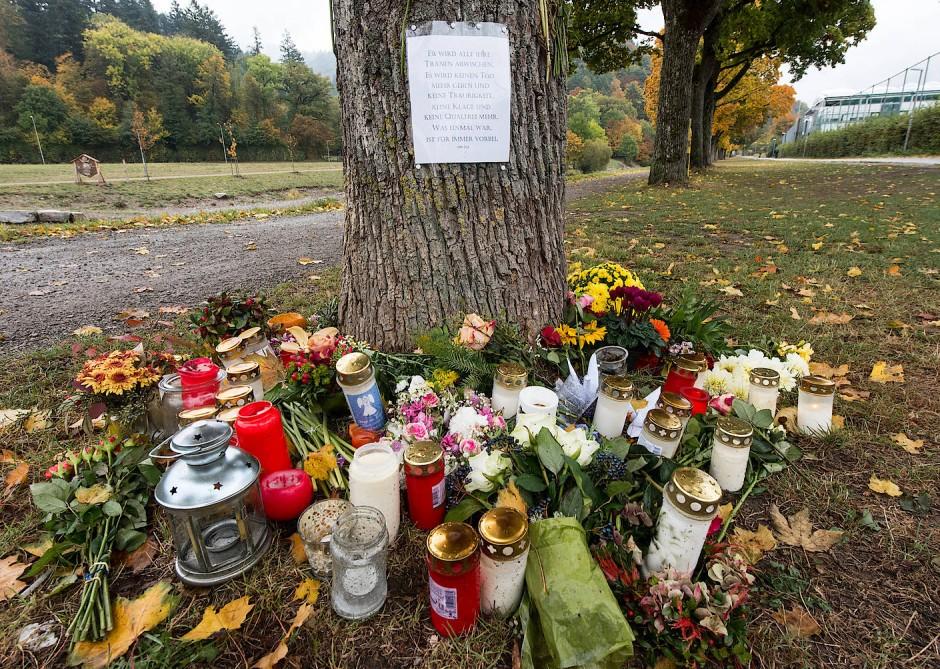 Blumen und Kerzen zum Gedenken an die ermordete Medizinstudentin Maria L. vor einem Baum am Ufer der Dreisam in Freiburg