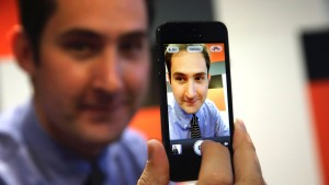 Systrom, chief executive of Instagram, displays his photo on a mobile phone during an interview with Reuters at the LeWeb technology conference in Aubervilliers