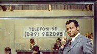 """Moderator Eduard Zimmermann, 1972, zu sehen mit einer typischen Handbewegung im Studio der ZDF-Sendung """"Aktenzeichen XY ungelöst""""."""