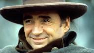 """Mit breiter Krempe und süffisantem Lächeln: Claude Brasseur 1988 in """"Dandin"""" von Roger Planchon."""
