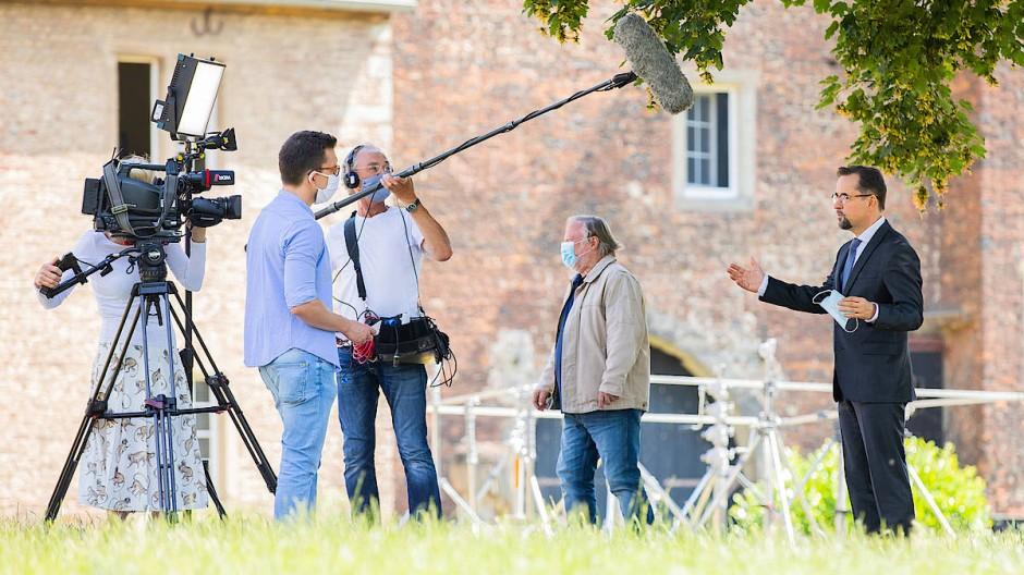 """Mit Mikro und Maske in Corona-Zeiten: Die Schauspieler Axel Prahl (Mitte) und Jan Josef Liefers beim Interview zu den Dreharbeiten für den """"Tatort""""."""