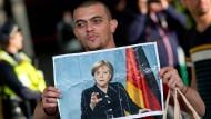 Ankunft auf dem Münchner Hauptbahnhof: Ein Flüchtling hat ein Bild von Angela Merkel im Gepäck.