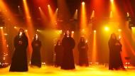 In schwarze Mönchsroben eingehüllt treten die Sänger des Chors Gregorian heute Abend auf die Bühne.