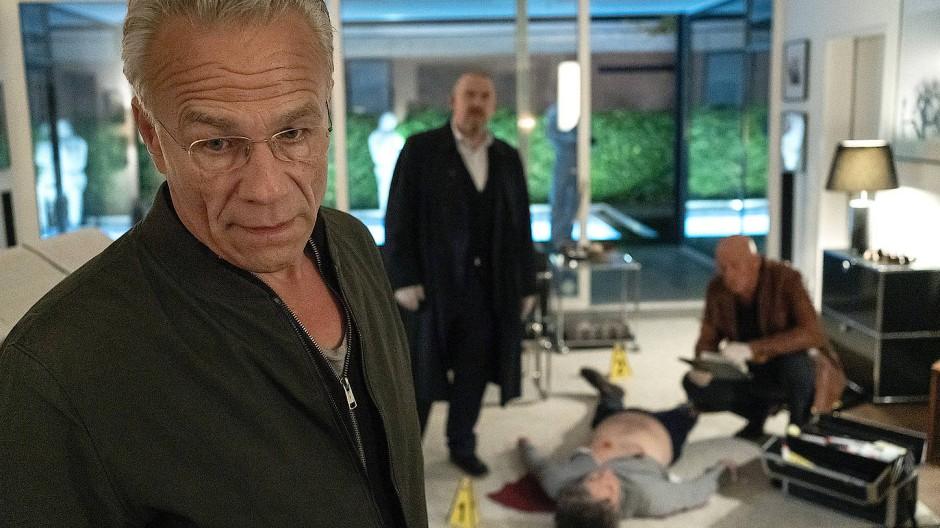Max Ballauf (Klaus J. Behrendt, vorn) ist im Dienst, aber nicht richtig da. Er wendet sich ab, während Rechtsmediziner Dr. Joseph Roth (Joe Bausch) und Freddy Schenk (Dietmar Bär) die Leiche von Prof. Krüger (Thomas Fehlen) untersuchen.