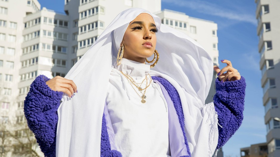 Eine junge Frau, die sich so selbstbewusst inszeniert, dass sogar die HLM-Wohnsilos der Pariser Vorstädte im Hintergrund frisch wirken.