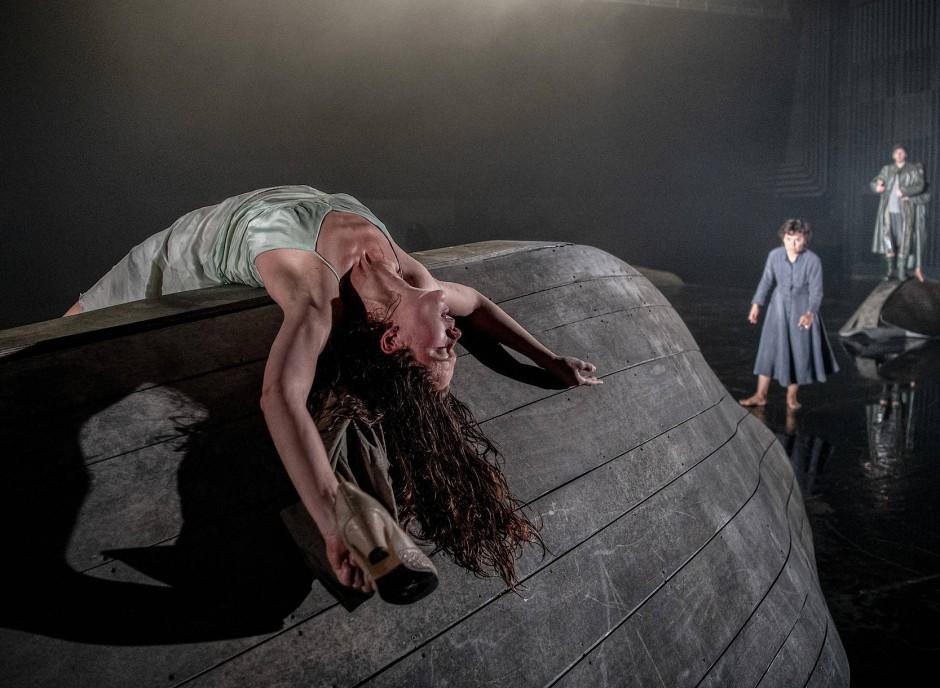 """Hingestreckte Puppen auf umgekehrten Ruderbooten: Szene aus """"Trilogie"""" von Jon Fosse in der Regie von Luk Perceval"""