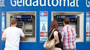 Kunden stehen an Bankautomaten um sich mit Bargeld einzudecken.