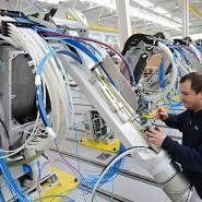Ein Mitarbeiter des Anlagenbauers Dürr arbeitet an einem Lackierroboter.