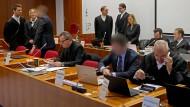 Die Angeklagten (3.v.l, und 2.v.r) und ihre Verteidiger im Cum-Ex-Strafprozess. Im Hintergrund Vertreter verschiedener Banken.
