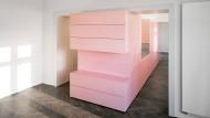 Statt Flur: In dem rosa Riegel stecken Bad, Küchenzeile und viel Stauraum.