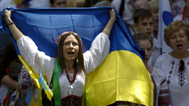 "Woman dressed in traditional Ukrainian clothing vyshyvanka holds national flag as she takes part in ""March in vyshyvankas"" in Kiev"