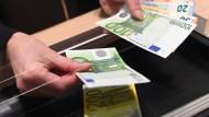 Ein Bankmitarbeiter zahlt Bargeld am Schalter aus