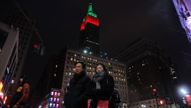 People walk near The Empire State Building as it is lit up in red and green on Christmas day in New York