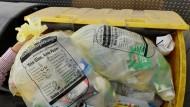 Ein Gelber Sack wandert in eine Abfalltonne