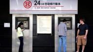 Chinesin zerlegt Geldautomaten