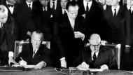 Der französische Staatspräsident Charles de Gaulle (r) und der deutsche Bundeskanzler Konrad Adenauer unterzeichnen am 22.01.1963 im Élysée-Palast in Paris den deutsch-französischen Freundschaftsvertrag.