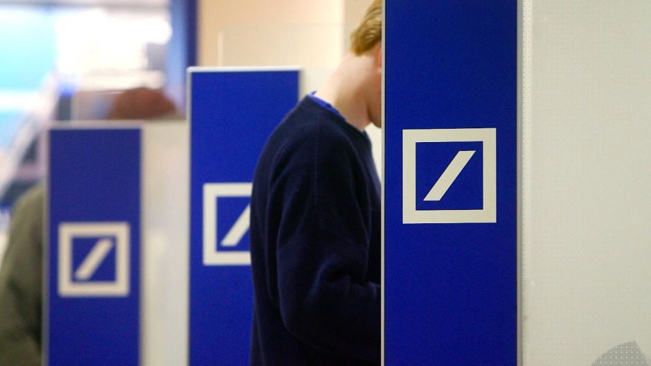 Ein Kunde hebt bei der Deutschen Bank Geld ab. Jetzt kann er auch bei dem Institut per vollautomatischen Anlageberater investierenn.