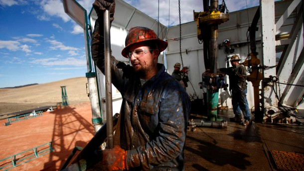 Roughneck Brian Waldner is covered in mud and oil while wrestling pipe on a True Company oil drilling rig outside Watford