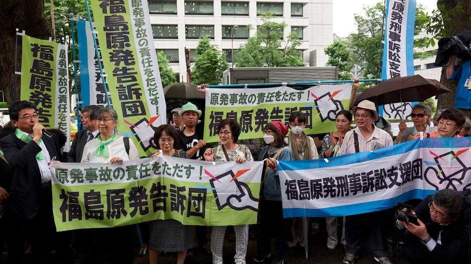 Demonstranten vor dem Bezirksgericht in Tokio, in dem am Freitag der erste strafrechtliche Prozess gegen ehemalige Spitzenmanager von Tepco wegen des Atomkraftwerksunglücks in Fukushima Daiichi begann.