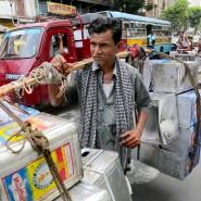 Ein indischer Arbeiter trägt Metallcontainer in Kalkutta.