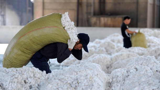 A worker carries a sack of cotton at a cotton purchasing station in Wuhu