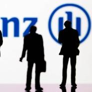 """Ein """"Großer"""" in der Versicherungsbranche: Kleine Plastikfiguren vor einem Allianz-Logo"""