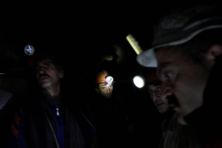 Nur das Licht ihrer Helmlampen beleuchtet den Arbeitsplatz der Bergmänner unter Tage.