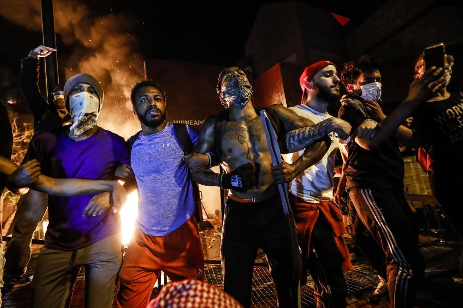 In den Straßen die Wut: Demonstranten bauen sich vor dem brennenden Minneapolis Police Department auf.