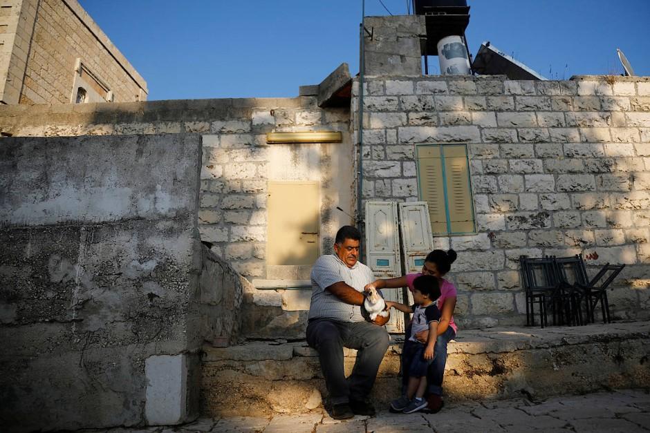 """Der palästinensische Bauer Azmi Musleh spielt mit seiner Tochter und seinem Enkel vor seinem Grundstück in Ein Yabrud, nahe der Siedlung Ofra mit einem Hasen. """"Das Land ist meine Herz und meine Seele. Es ist das Herz und die Seele meiner Familie. Wir bauen hier seit Generationen Sesam, Feigen und Oliven an."""""""