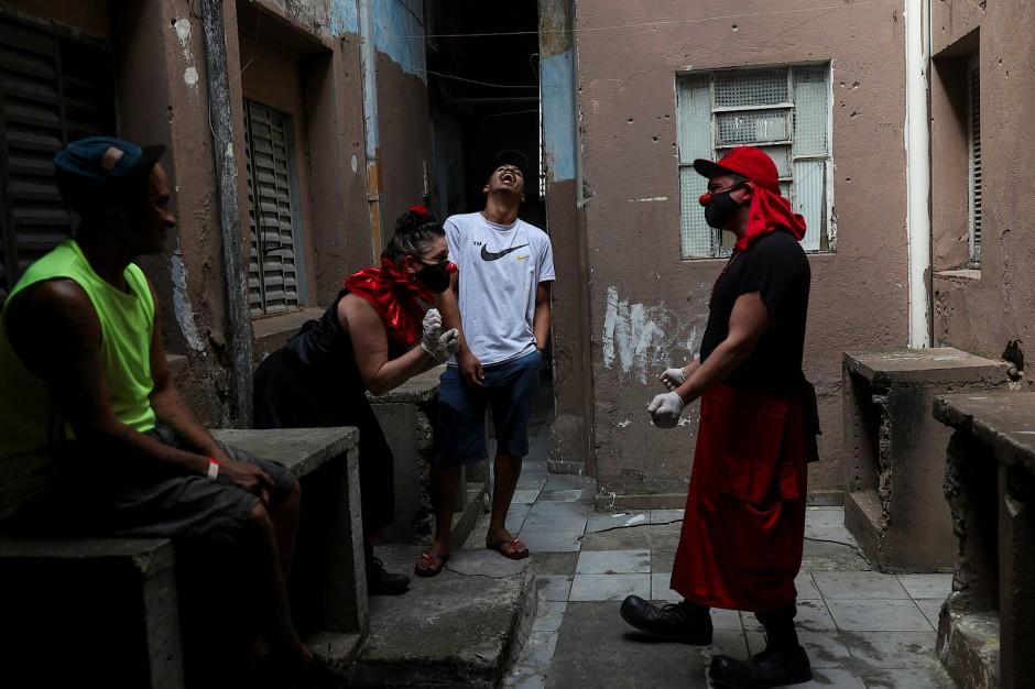 Flavio Falcone und Andrea Macera sprechen im Hinterhof mit jungen Männern.