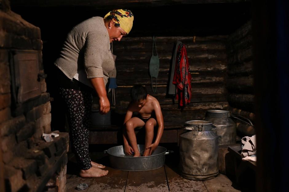 Mutter Elmira hilft ihrem Sohn Ravil Izhmukhametov am Abend beim Waschen.