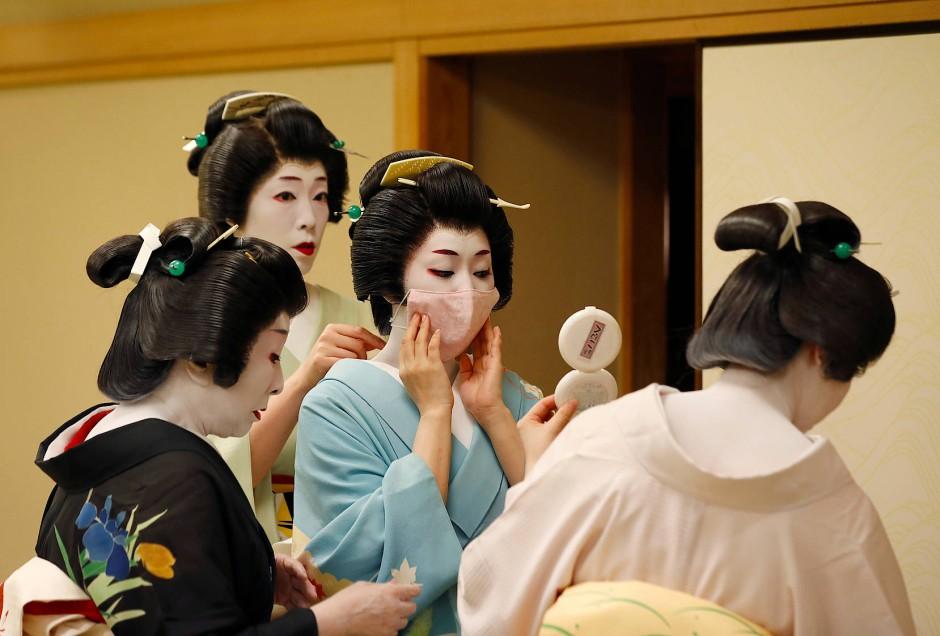Eine ältere Geisha hilft der jungen Koiku eine Maske aufzusetzen.
