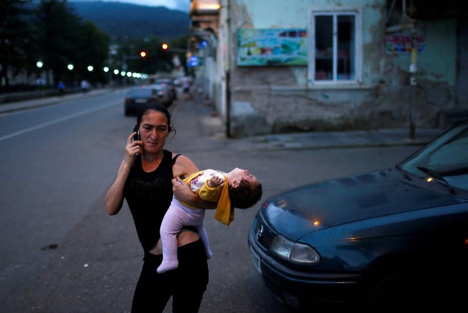 In der Abenddämmerung steht eine Frau mit ihrem Kind auf der Straße in Tkibuli und telefoniert.