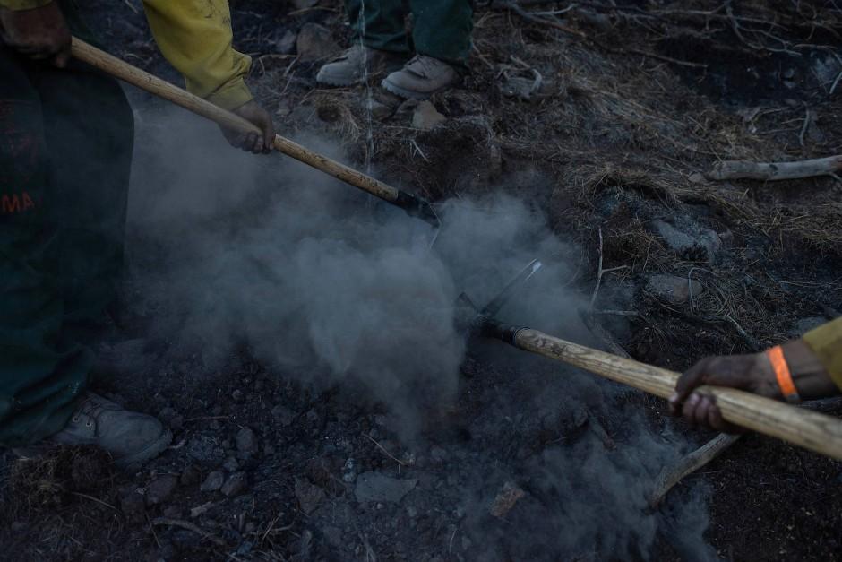 Die Männer versuchen einen schwelenden Brand einzudämmen.