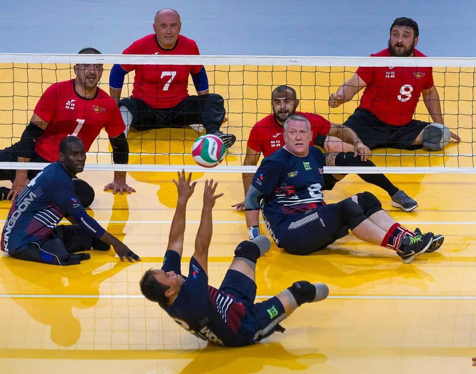 Die Spieler beim Sitz-Volleyball geben beim Endspiel zwischen Georgien (rote Trikots) und Großbritannien (blaue Trikots) ihr Bestes.