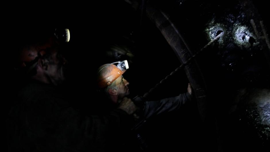 Minenarbeiter unter Tage: Eine kleine Kopflampe beleuchtet den Arbeitsplatz.