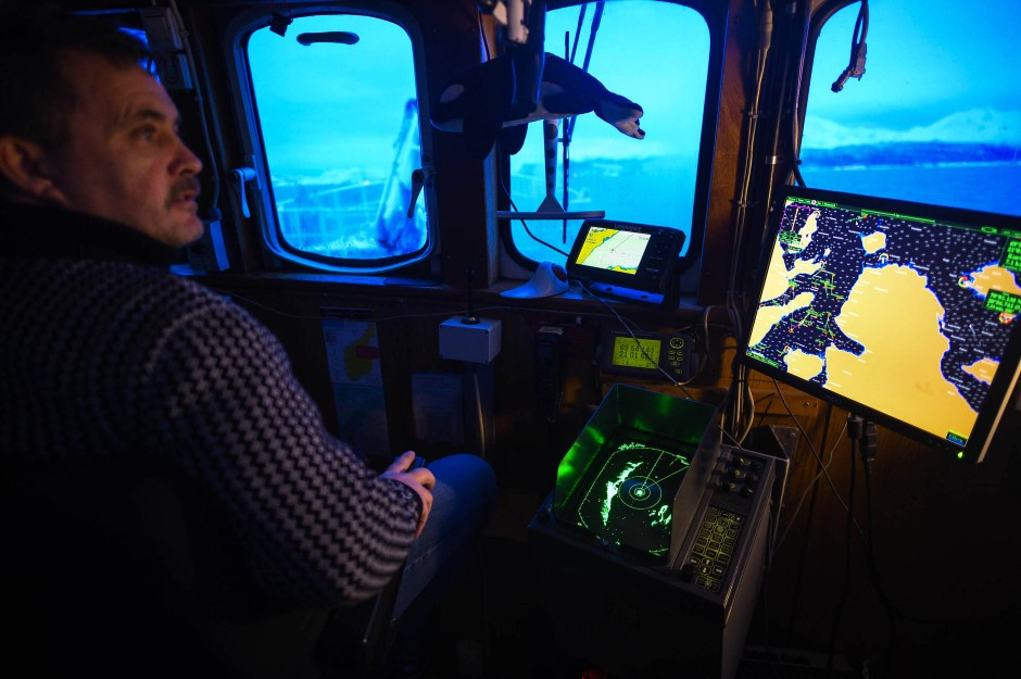 Torbjorn Larsson, der 1. Offizier der M/S Sula,  hält von der Brücke aus Ausschau nach Walen im Reisafjord.