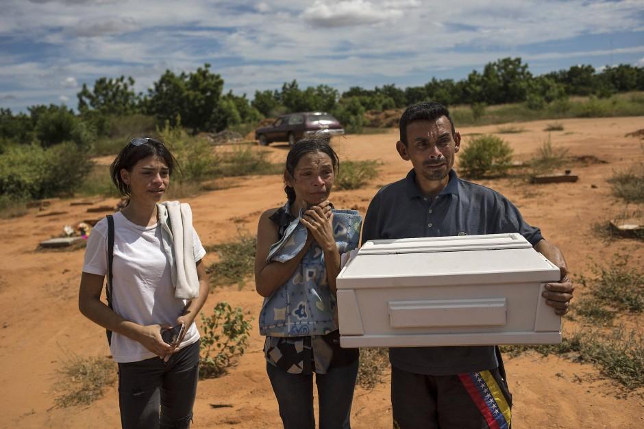 Roberto Parra trägt einen kleinen Sarg mit den sterblichen Überresten seines 19 Tage alten Sohnes. Der kleine Junge sei nach der Geburt wegen Lungenproblemen in einem öffentlichen Krankenhaus gestorben. Obwohl seine Frau den Jungen mit Atembeschwerden entbunden hatte, wurde ihnen gesagt, sie sollten ihn mit nach Hause nehmen, da er im Krankenhaus kränker werden könnte, wenn sie bleiben würden.