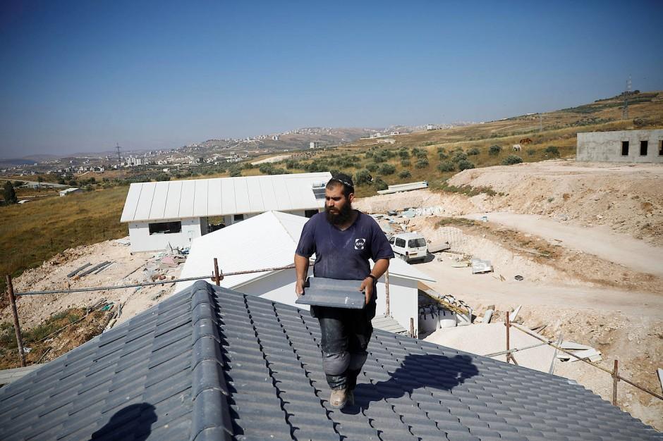 Ein Israeli deckt ein Dach auf einer Baustelle der Siedlung Havat Gilad im Westjordanland.