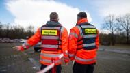Zwei Mitarbeiter des Deutschen Roten Kreuzes regeln im Drive-In-Impfzentrum in Bremervörde den Verkehr.