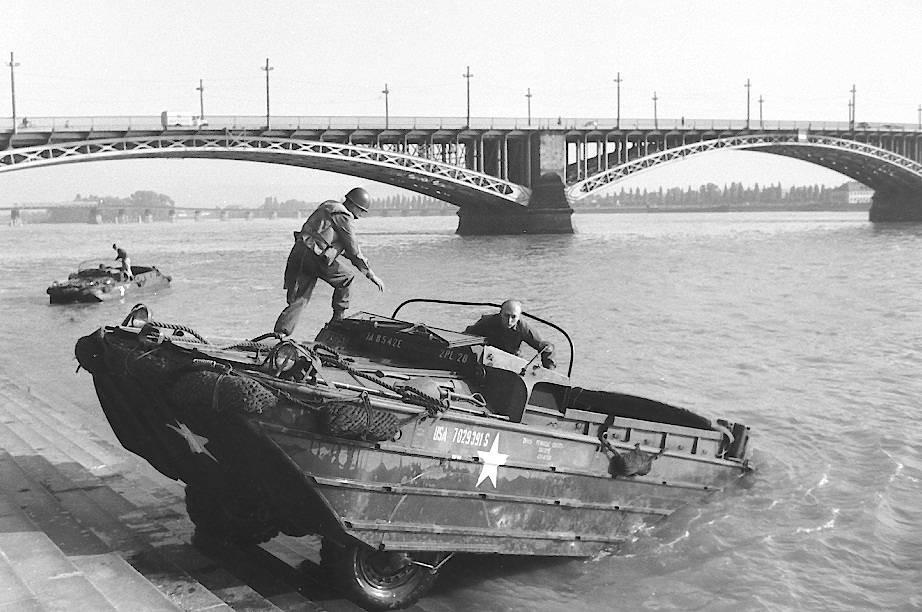 Amphibienfahrzeug im Rhein – Ein US-Amphibienfahrzeug erklimmt die Treppen am Rheinufer, oberhalb der Theodor-Heuss-Brücke, nach einer Übungsfahrt. Die verhältnismäßig kleine Einheit war nahe dem Rüsselsheimer Bahnhof stationiert.
