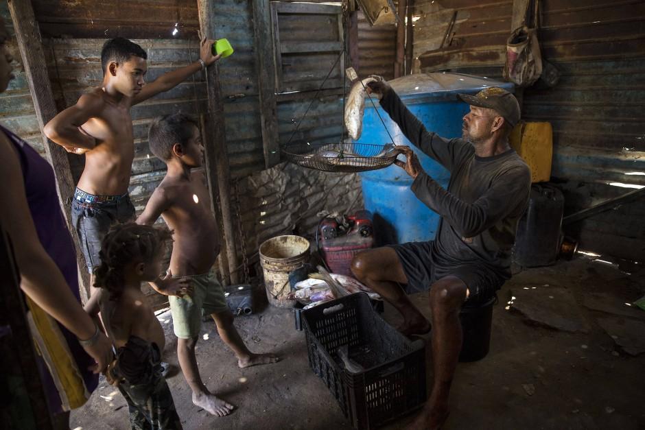 Alejandro Elizalzabal wiegt seinen Fang. Was die Familie nicht selbst braucht, wird zum Verkauf angeboten.