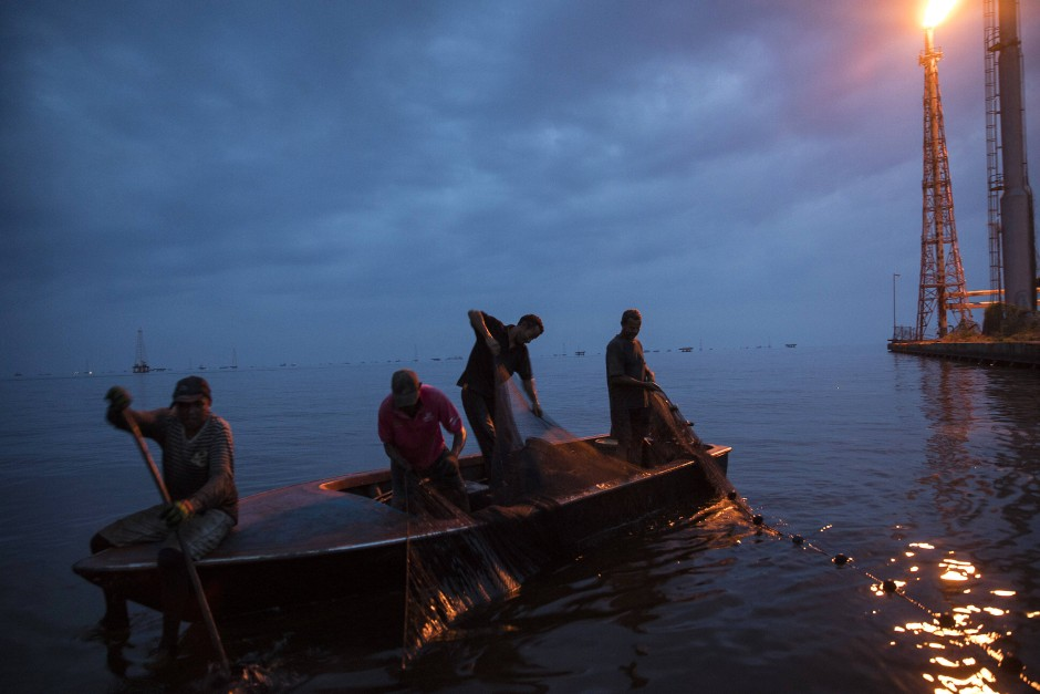 Im Schein der Gasfackel am Terminal von La Salinas ziehen Fischer Netze mit Krabben ins Boot.