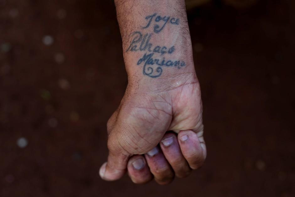 Jailson Antonio de Oliveira zeigt der Fotografin seine Tätowierung, die er sich für Flavio hat stechen lassen.