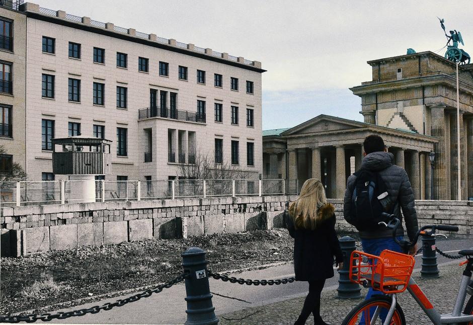 Tiergarten angrenzend an Mitte, Brandenburger Tor von der Ebertstraße aus fotografiert: Während des Zweiten Weltkrieges war das Brandenburger Tor stark beschädigt worden. Nach dem Bau der Mauer stand das Berliner Wahrzeichen unzugänglich mitten in den Sperranlagen. Auf der Westseite konnten Berlin-Besucherinnen und -Besucher Aussichtspodeste besteigen und einen Blick über die Mauer auf das Tor und in den Ostteil der Stadt werfen. Auf der Ostseite gab es auch ein Podest, allerdings nur für Staatsgäste. In der Nacht vom 9. auf den 10. November 1989 feierten Berlinerinnen und Berliner aus beiden Teilen der Stadt unter dem Brandenburger Tor den Fall der Mauer. Am 22. Dezember 1989 wurde das Brandenburger Tor unter dem Jubel von mehr als 100.000 Menschen wieder geöffnet. An diesem Ereignis nahmen Bundeskanzler Helmut Kohl, Außenminister Hans-Dietrich Genscher, der Regierende Bürgermeister von Berlin, Walter Momper, und DDR-Ministerpräsident Hans Modrow teil. Heute gilt das Brandenburger Tor als das Symbol für die Deutsche Einheit.