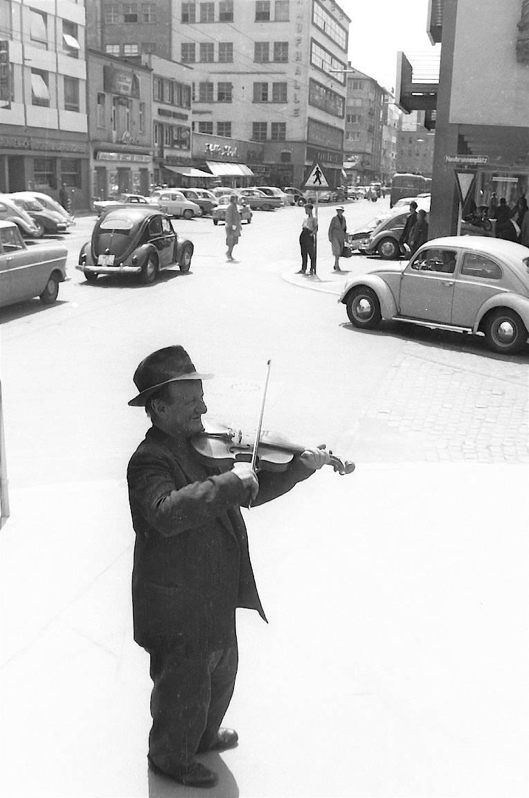 Geigerfränzje -  Das Geigerfränzje, eigentlich Franz Josef Schneider (30.4.1893 - 6.4.1962), spielt auf dem Neubrunnenplatz (Aufnahme ca. 1958). In der Zeit nach dem Zweiten Weltkrieg zog er durch die Stadt, spielte an Plätzen und in Hinterhöfen und verdiente seinen Lebensunterhalt mit dem Geigenspielen. Er war ein Mainzer Musiker und Original.